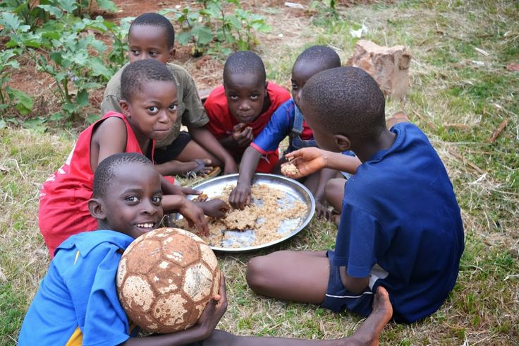Kids in Africa taking a lunch break from their soccer game.