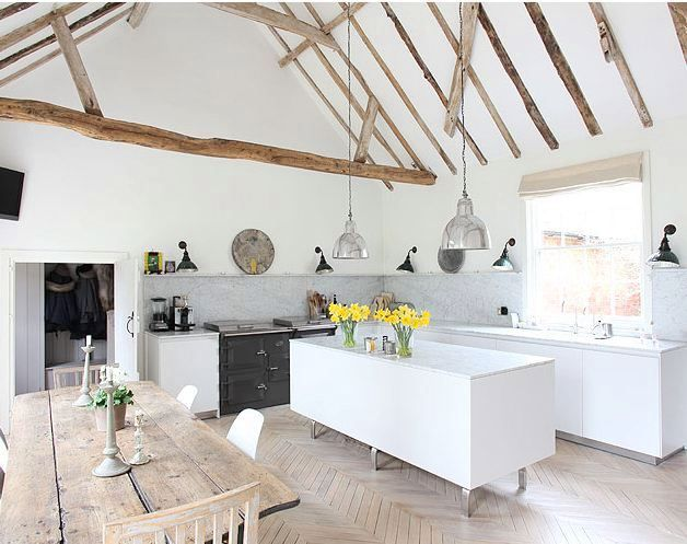 Kitchen with exposed wood beams, pendant lights, an island - like the very light colour scheme