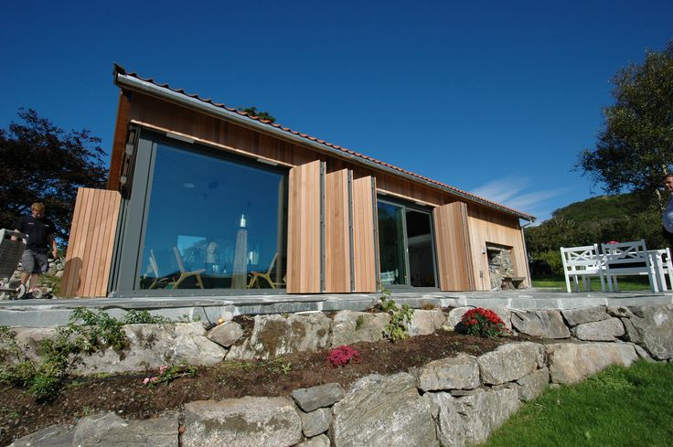 Cladding in red cedar wood.  The folding shutters are closed. Architect: Marita Hamre