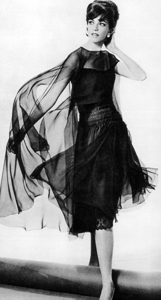 Chanel model, Vera Valdez, is wearing dress of black chiffon hemmed with fine Chantilly lace,a long ruched bodice, and sheer cape that is short in front and flares in back, photo by Georges Saad, 1961