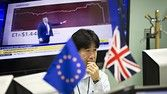 "An employee works in front of computer monitors near a European Union (EU) flag, left, and a British Union Flag, also known as a Union Jack, at a foreign exchange brokerage in Tokyo, Japan, on Friday, June 24, 2016. The pound tumbled with the euro and U.K. equity index futures after early results from Britain's referendum on membership of the European Union put the ""Leave"" campaign ahead, suggesting the risk of a so-called Brexit is greater than opinion polls implied. Photographer: Tomohiro…"