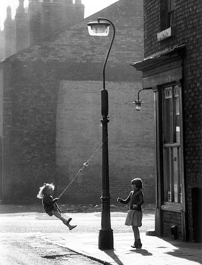 """Shirley Baker - """"Girls swinging on a lamppost"""", Manchester, 1965"""