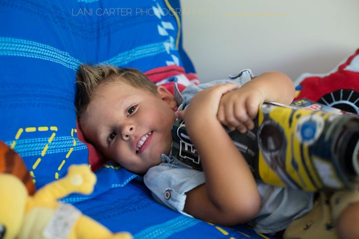 Boy hugging a magazine on his bed. Lifestyle photography. www.lanicarter.com
