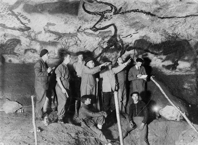 Le paléontologue et préhistorien français Henri Breuil observe le panneau des Aurochs dans la salle des taureaux de la grotte de Lascaux à Montignac, en compagnie d'autres archéologues et des deux des adolescents qui ont découvert la grotte