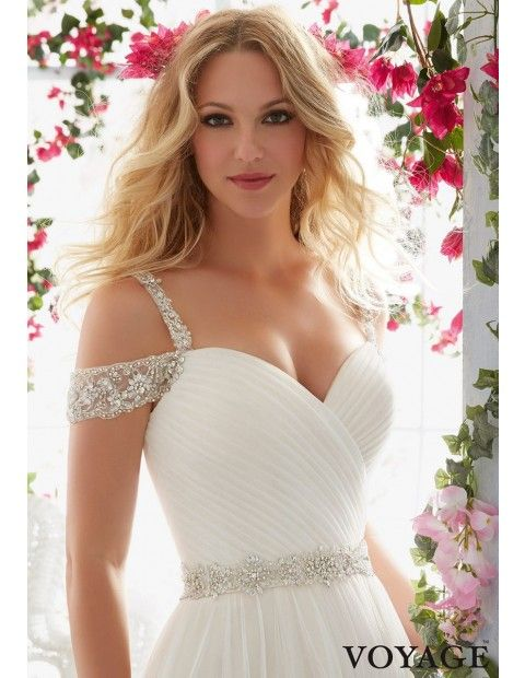 This Mori Lee 6814 wedding dress features a sweetheart neckline and beaded embroidered shoulder straps complemented with off-the-shoulder sleeves. Created in soft net this gown has an asymmetrically pleated, surplice bodice with semi-open back. Covered buttons accent the back, running below the crystal beaded waistband. The layered skirt and chapel train are lightly gathered and complete the A-line silhouette.