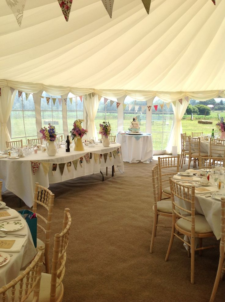 Bunting is used to decorate the head table in this country wedding marquee in Hampshire..