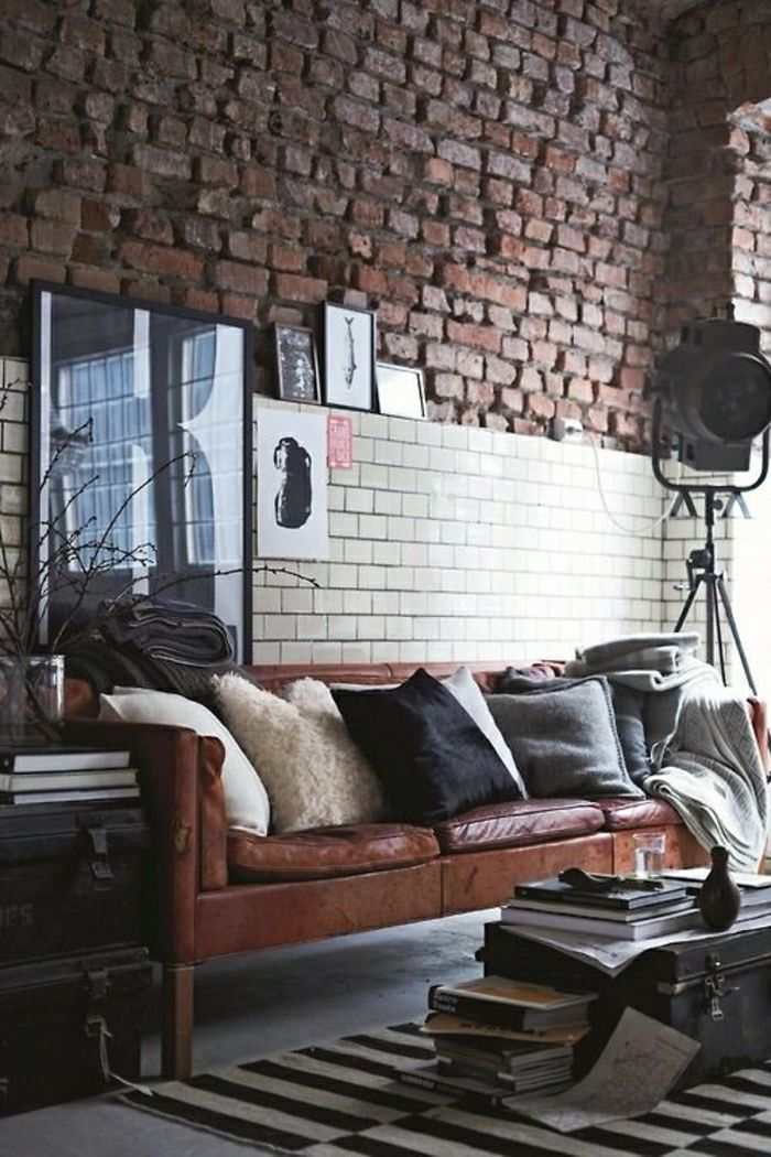 canapé en cuir marron, coussins décoratifs, mur de briques rouges, salon vaste, lofts
