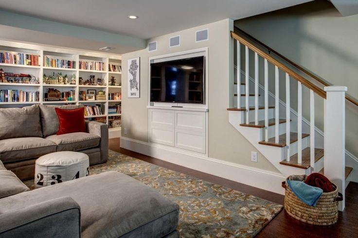 In this new staircase to a finished basement, we used the wall adjacent to the stairs to hide a TV and the area below it for media equipment