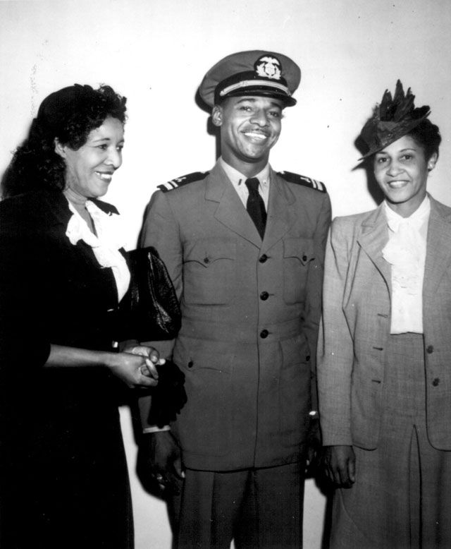 World War 2 African Americans Merchant Marine Lt.(jg.) Stanly Marlowe Smith, U.S. Maritime Service; [Mrs. Marion H. Elliott] Assistant Executive Secretary of the National Council of Negro Women; and Mrs. B.L. Derrick, Chairman. Lt. Smith is pictured at a war bond rally in Washington, DC, where he spoke and was honored. August 8, 1944. 357-G-83-4308.