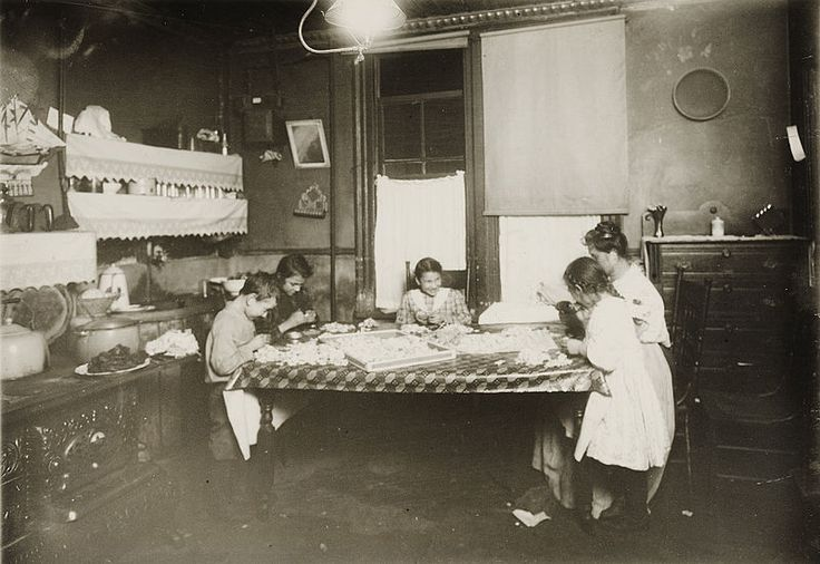 Children working at night. Lamp glows at the ceiling.  7:30 P.M. January 29, 1912. Making violets, and they often work later. Pollinni family, 5 Carmine St., New York, NY, living in a rear tenement. The six year old helps some. The eight, ten, and twelve year olds work later than this at times. Brothers, 15 and 17 years old, work in factory.