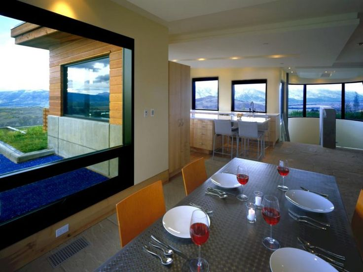 Dining Room: Contemporary Dining Space Highlighting Stainless Steel Dining Table And Splendid Mountain Views. modern dining room set. stainless steel dining table. orange dining chair. open floor dining room. mountain view dining room. dark framed window.