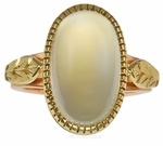 A spectacular gem Indian moonstone cabochon, nearly 10 carats in weight perfectly bezel (notice the serrated hand done edge) set in 18k yellow gold with acanthus leaf decoration down the side of the shank. The leaf pattern in all hand done and highlighted by the rose gold shank. Simple yet elegant!
