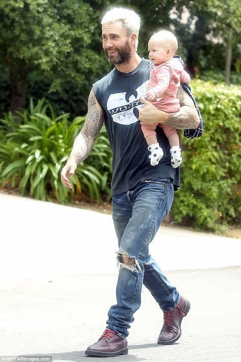 Family man: Adam Levine, 37, looked like a proud dad as he carried Dusty Rose, seven months, into a friend's house alongside supermodel wife Behati Prinsloo, 27