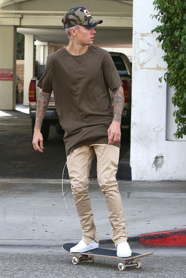 Justin Bieber wearing  New Era x Xlarge 9forty D-Frame Front Patch Woodland Hat, Vans Classic Slip-On Shoes, Stampd Boxy T-Shirt, Fear of God The Drawstring Trousers