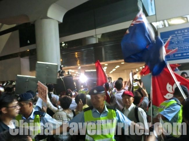 Flag-waving pro-government patriots clash with a large crowd of pan-democrat protesters outside at the HKTV protest. (The blue Hong Kong colonial flag is being waved by an anti-government pan-democrat.)  Read the full article here: http://thechinachronicle.com/hong-kong-tv-vote-delayed-aggressive-protesters-surround-legislative-council/