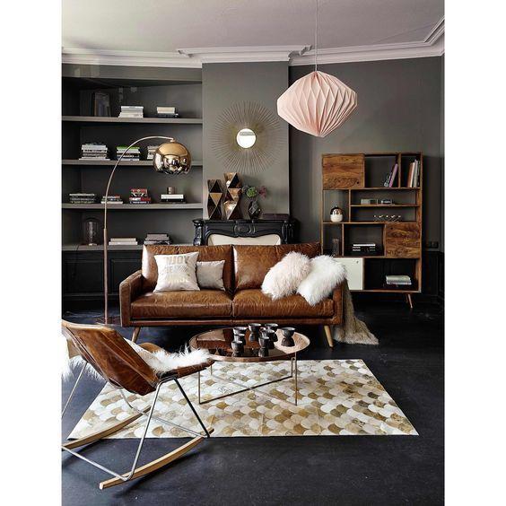 Une suspension rose, un canapé en cuir vieillit et des peux de bêtes pour un style mix and match très réussi