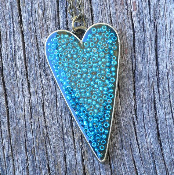 Making my own version tomorrow.  Round bezel cup, blue/aqua/green mixed seed beads, and ModPodge Dimensional Magic goo.