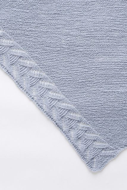 """""""I wanted to design a minimalist blanket shawl without superfluous details — useful all the year long, a sort of cozy envelope. The wrap you like to have always nearby, perfect for rainy afternoons on the couch or cool evenings outside. I added a subtle feminine touch by working a lace motif along two edges."""" – Nadia Crétin-Léchenne"""