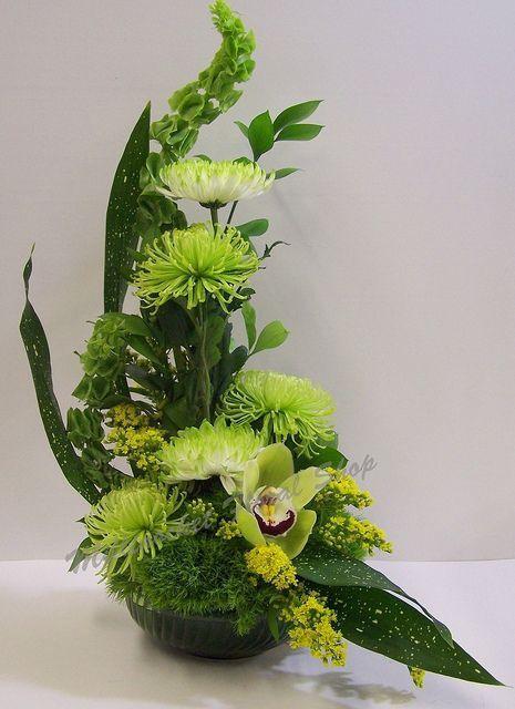 Media luna con 5 crisantemos verdes, 2 campanas de Irlanda, 1 orquídea como punto focal y follaje.