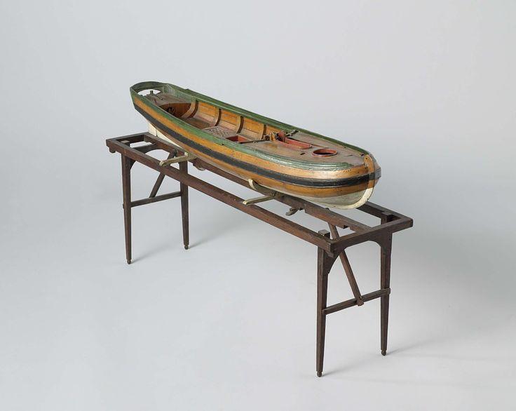 Anonymous | Model van een vissersboot, Anonymous, 1820 - 1865 | Gepolychromeerd spantmodel van een eenmast vissersboot, zonder tuig en op inklapbare standaard. Het is een elegante romp met gebogen, gekrulde voorsteven, gewrongen spiegel met wulf en klein, open hek; het roer heeft een breed blad en ronde roerkoning en is met spijkers aan het model bevestigd. De boot heeft een voordek met rond luik, een grote open kajuit met daarin een driedelige bun, en een achterplecht. De zeeg loopt naar…