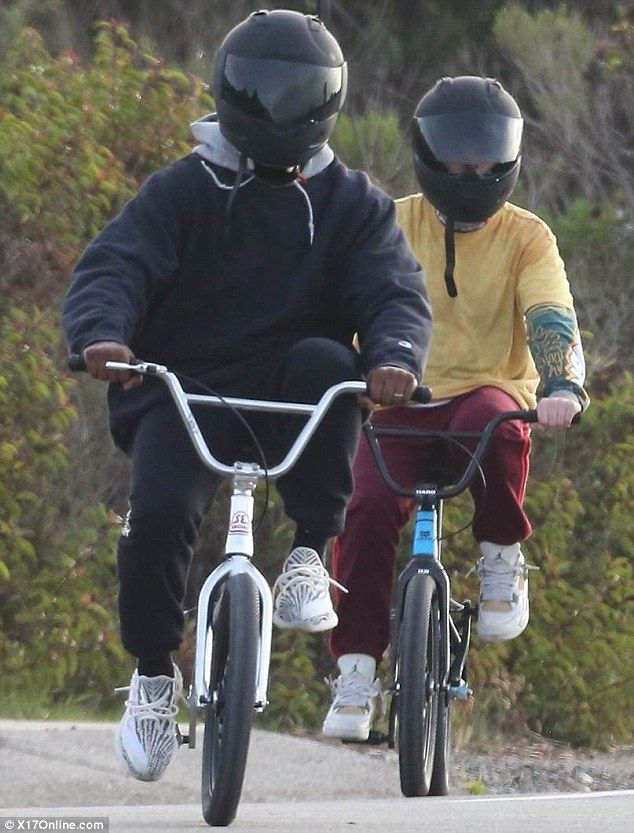 Keeping up: The 39-year-old rapper - who wore a full-faced motorcycle helmet - was joined by two chums as he pedalled along in his yet-to-be-released Adidas Yeezy Boost 350 v2 trainers