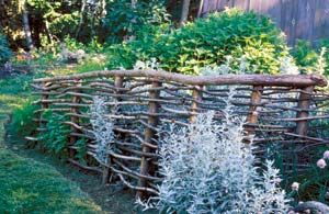 rustic wood fence made of tree branches. Possibility for butterfly garden?
