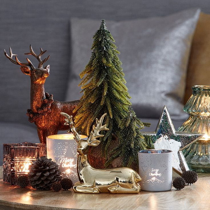 A side table is the perfect space to gather a cluster of Christmas pieces. Pair enchanting reindeer with miniature trees and glowing tea lights to bring a touch of Christmas magic to any night. #christmas #christmasdecorating #bedbathntable