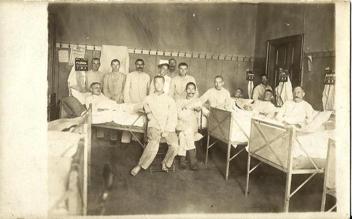 """Klassenräume wurden zu Krankenzimmern. Verwundete Soldaten werden im Singener Hegau-Gymnasium behandelt. In der Mitte mit Schnauzbart Heinrich Wolf. Nach dem Krieg übernahm er in Singen den Gasthof """"Sonne""""."""