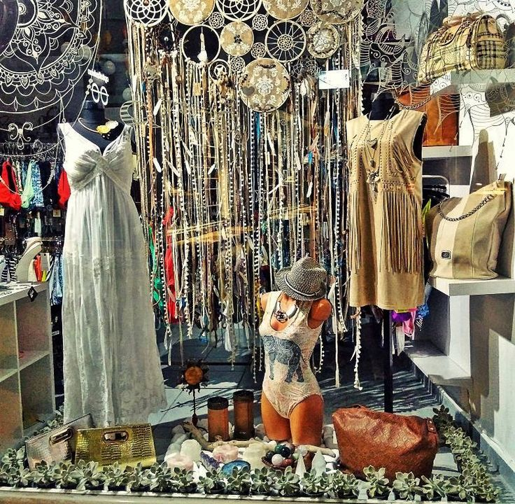 Absolutely stunning summer boho window display, in a boutique in Salamis, Greece! A large and wonderful dream catcher with hundreds of ribbons and beads stands behind as a back, while in the front, there is a border made of succulent plants and large white pebbles.