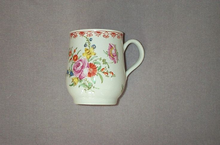 """A Bow bell shaped  mug with a grooved handle and painted with a bouquet of flowers beneath a flower scroll and diaper border.  Unmarked  Circa 1765  Height 3 3/4"""""""