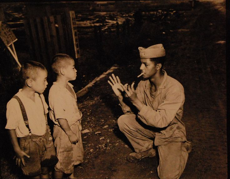 With only one phrase in his Japanese vocabulary, Marine Corporal Paul K. Meeres resorts to sign language to make himself understood in a conversation with two Japanese children at Sasebo, Japan. Photographed by Staff Sergeant John Brenneis, 1 October 1945.