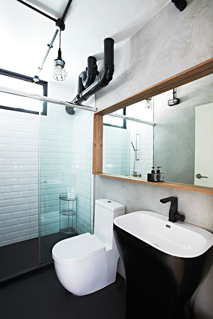 The black pedestal washbasin and matching water faucet stand out in the bathroom. The exposed pipes were also painted black to turn an eyesore into a feature.
