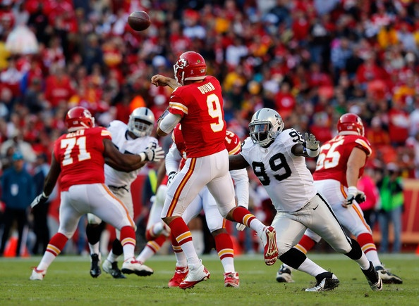 Quarterback Brady Quinn #9 of the Kansas City Chiefs is hurried by defensive end Lamarr Houston #99 of the Oakland Raiders at Arrowhead Stadium on October 28, 2012 in Kansas City, Missouri.