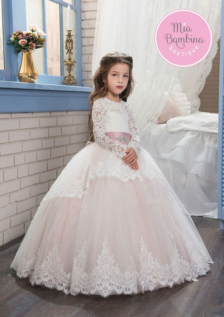 The Arlington ball gown style flower girl dress has a princess appearance. The lace bodice features long floral lace sleeves, a tie-back waist and a lace corset for added adjustable fit. A rhinestones
