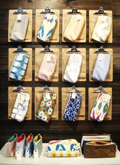 Our display of Aeolist handmade clutches on our plank wood wall using simple clip boards from staples.
