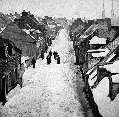 """""""Une rue enneigée de Québec (Québec, Canada) à l'hiver 1872. Il s'agit de la rue aujourd'hui nommée Saint-Patrick (Saint-Patrice) [...]. Sur la photo, la rue est vue en direction ouest. On distingue dans le coin supérieur droit de la photo les deux clochers de l'ancienne église Saint-Jean-Baptiste, qui sera détruite dans l'incendie de 1881. Tout le quartier fut détruit lors de l'incendie de 1881. La rue ne ressemble plus aujourd'hui à ce qu'on voit sur cette photo."""""""