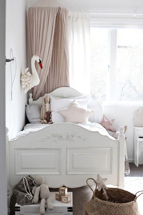 Białe rzeźbione łóżko w pastelowym pokoju dziecięcym