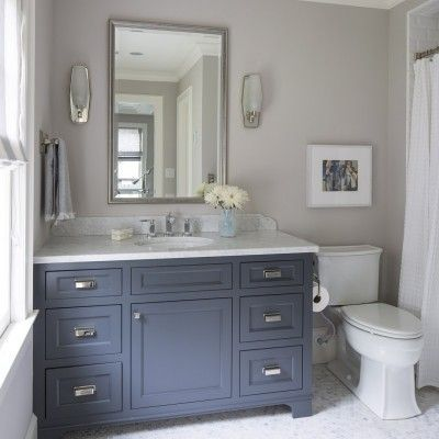 bathroom with blue-gray vanity, framed mirror and wall