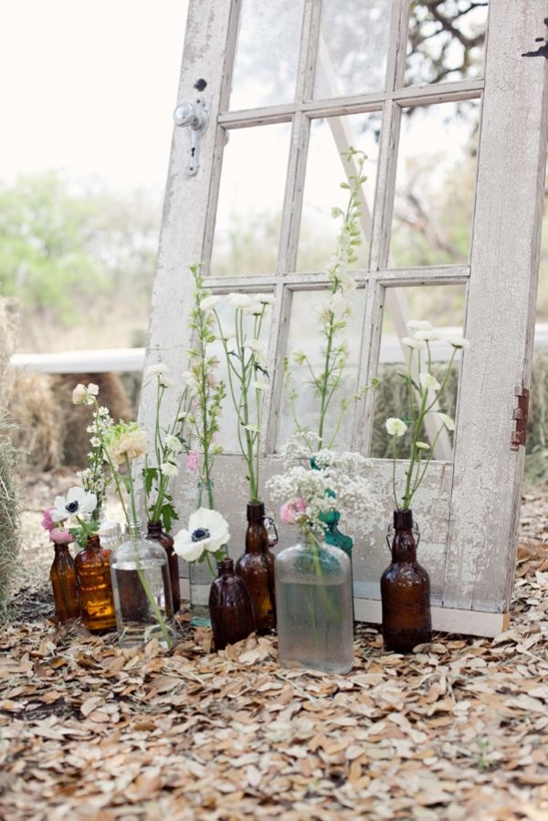 Vintage door + re-purposed bottles used as vases= simply beautiful.  doors and weddings. vintage weddings. rustic weddings. outdoor wedding.