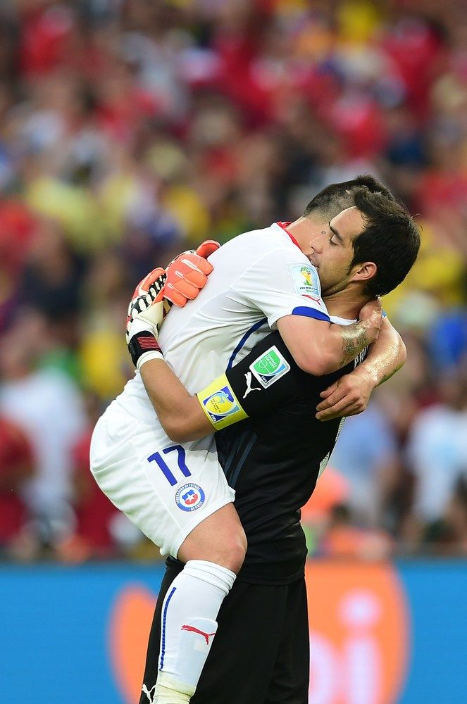 Spain Eliminated From World Cup With Devastating Loss To Chile - Chile's defender Gary Medel (L) celebrates with Chile's goalkeeper and captain Claudio Bravo after Chile scored their first goal during a Group B football match between Spain and Chile in the Maracana Stadium in Rio de Janeiro during the 2014 FIFA World Cup on June 18, 2014.