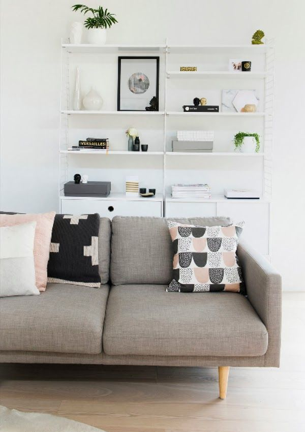 Neutral and pastel nude added into a grey and white Scandinavian living room. Love the large shelving unit holding loads of accessories.