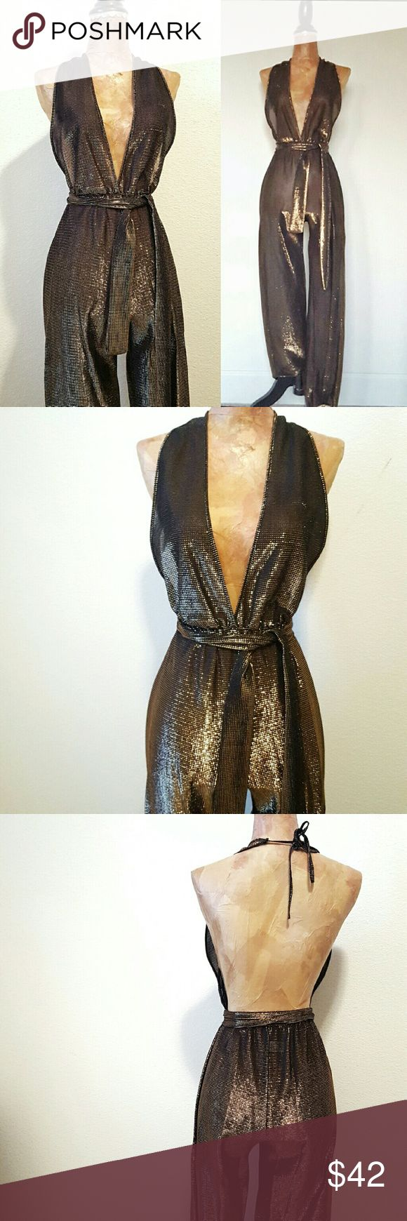 "Vintage 70s Disco Metallic Backless Jumpsuit A-mazing piece of vintage gold. Black with bronze metallic thread, semi- sheer fabric. Backless and halter top, ties at neck. Elastic at waist and ankles. Attached matching sash belt. Slightly cropped length on legs, approx. 30"". Waist is approx 10"" unstretched and 17"" stretched. Fantastic vintage condition. Fits xs/small depending on desired fit. Vintage  Pants Jumpsuits & Rompers"