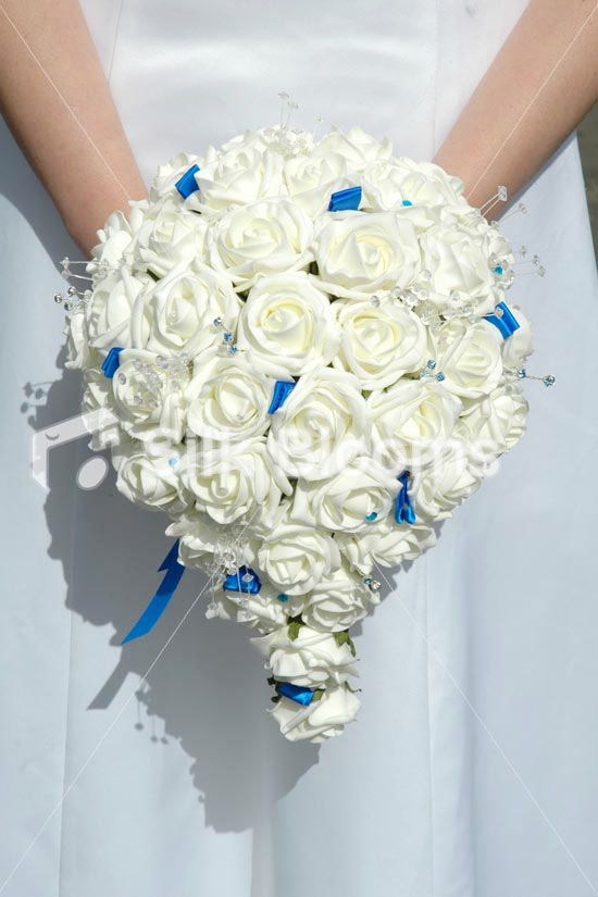 Top quality royal blue satin ribbon round the handle (can change). Luxury, large ivory rose teardrop bouquet. Ivory crystal wedding flowers. Absolutely beautiful, sparkling crystals & delicate royal blue crystal sprays. Truly stunning crystal ivory rose wedding bouquet in a teardrop shape. This will compliment any bride, truly stunning in every way.