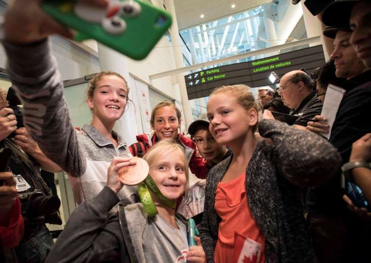 Canadian Olympic bronze medallist for rugby sevens Megan Lukan, back, poses for a selfie with fans as she is welcomed at the Toronto Pearson Airport in Toronto, on Aug. 23.