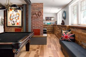 Industrial games room with exposed brick walls and reclaimed wood features