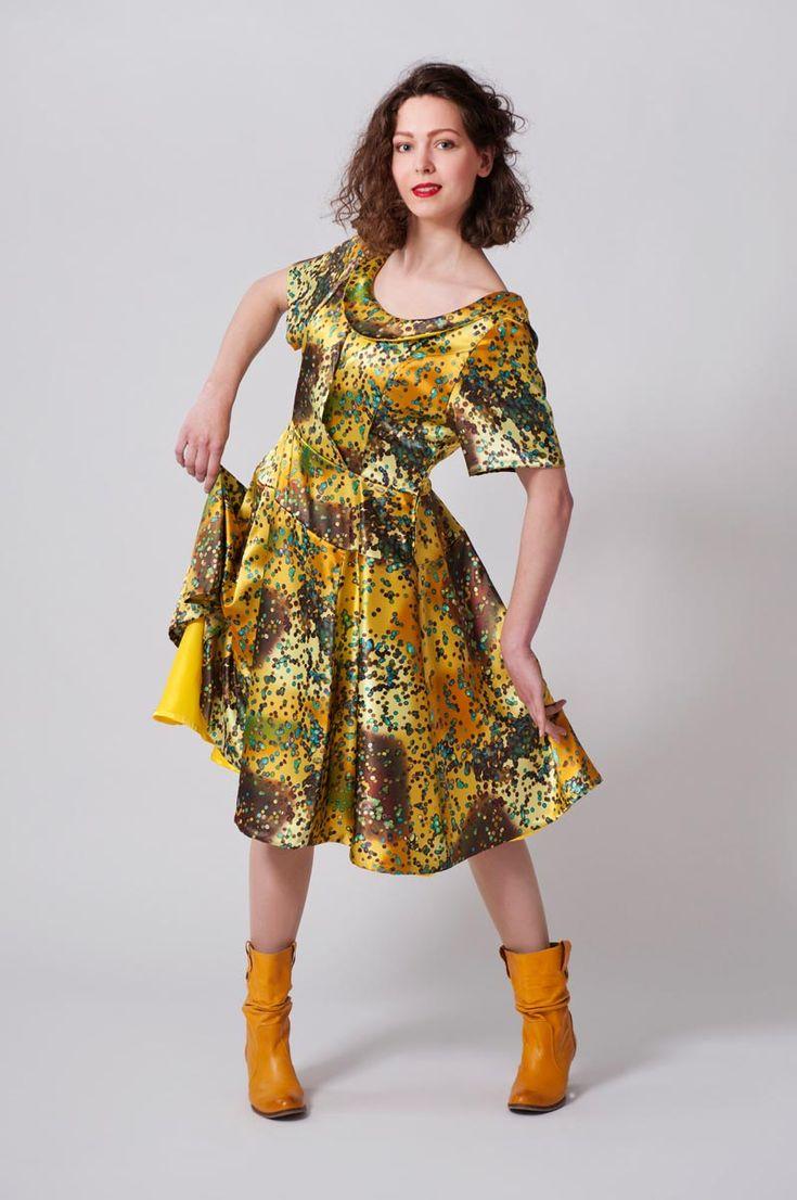 Gele satijnen jurk met overslagen tot in de taille, wijd rokgedeelte en asymmetrische kraag.