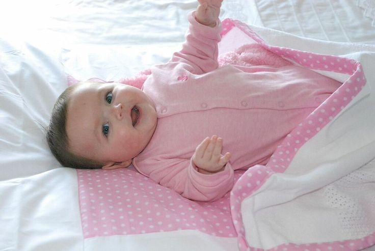 Pretty in pink - baby Jordan enjoying her pink Tom & Bella baby spots cot duvet cover and matching cotton cell blanket.