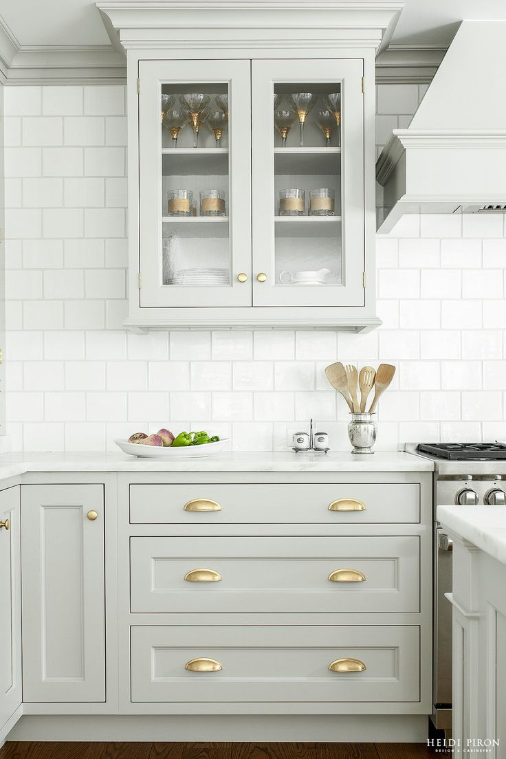 Gray cabinets with glass doors and gold hardware, white subway tile backsplash | Heidi Piron