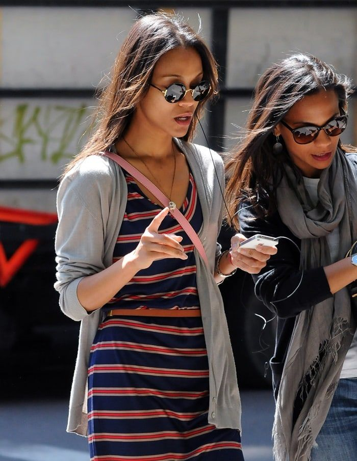 Zoe Saldana sharing an earbud headphone on an iPod with a friend while out and about in Manhattan on May 11, 2012