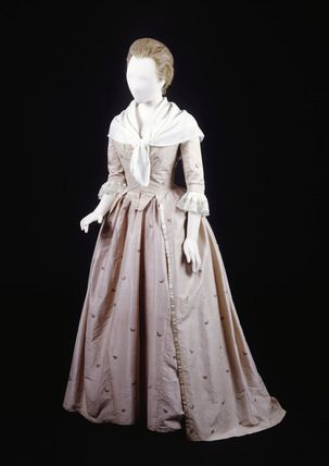 Silk open-skirt dress with matching peticot. The dress has a robe and matching underskirt. It is a pale mauve-pink silk of English manufactrure woven with a very small spot and with small flral sprays in various colours. The bodice's front edges meet and its centre back is lightly boned. The skirt front edges are bound with white silk ribbon. The tapes and loops make a 'polonaise' style skirt.     Date  1778 AD - 1885 AD